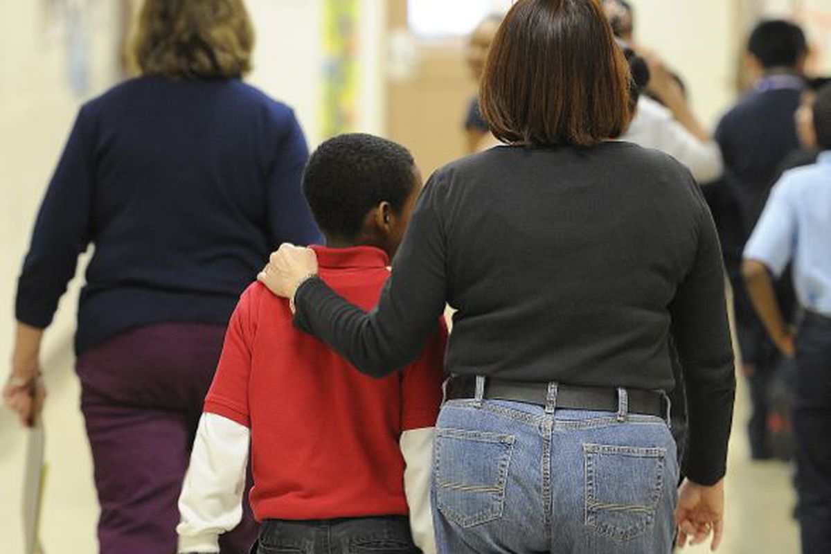 A teacher escorts a student to class at IPS School 90.