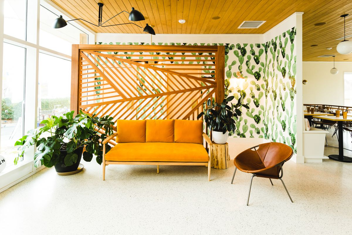 The entryway at Hello Sailor: a plant, couch, chair, and backdrop of cactus wallpaper