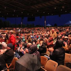 """Veterans in the audience in the pavilion at Bethel Woods Center for the Arts stand at the invitation of Lloyd Newell just before the Tabernacle Choir performance of """"Battle Hymn of the Republic."""""""