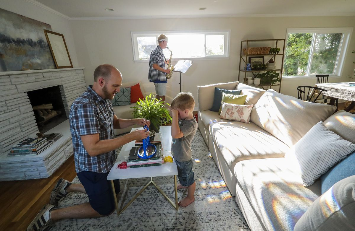 Jon Larsen plays with son George as his oldest son, CS, practices his saxophone at their home in Salt Lake City on Wednesday, Sept. 16, 2020.