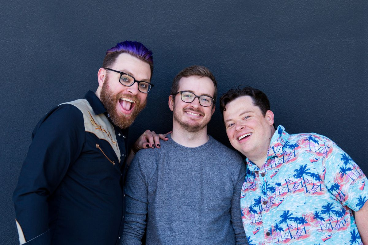 Travis, Griffin, and Justin Mcelroy standing against a blue background.