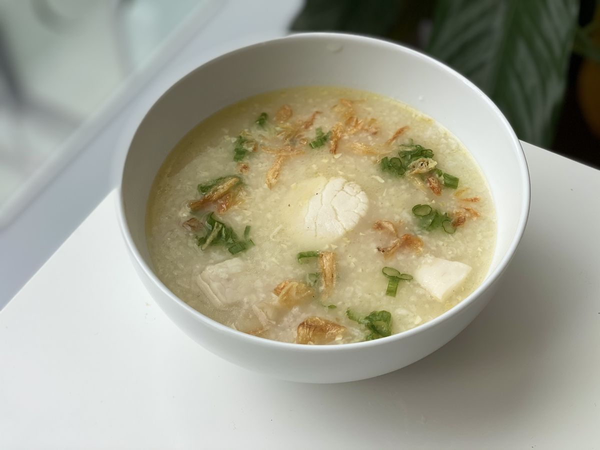 A Vietnamese-style scallop rice porridge with garlic, butter, scallion, and cilantro in a miso-colored broth
