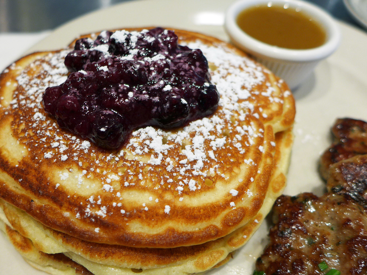 A stack of pancakes dusted with powdered sugar and topped with blueberry jam. A tiny bowl of syrup sits on the side.