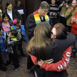 Laura Fernandez, in black, embraces her new wife, Chantel Buhler, after being married by the Rev. Curtis Price as 4-year-old Kayson Buhler averts his eyes in the Salt Lake County offices after a federal judge ruled that Amendment 3, Utah's same-sex marriage ban, is unconstitutional on Friday, Dec. 20, 2013.
