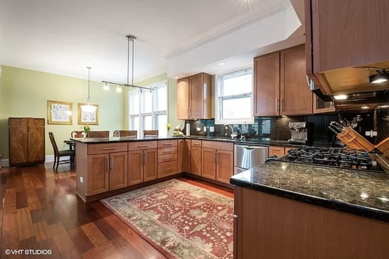 A large U-shaped kitchen with a dining area and wood cabinets topped by dark stone counters.