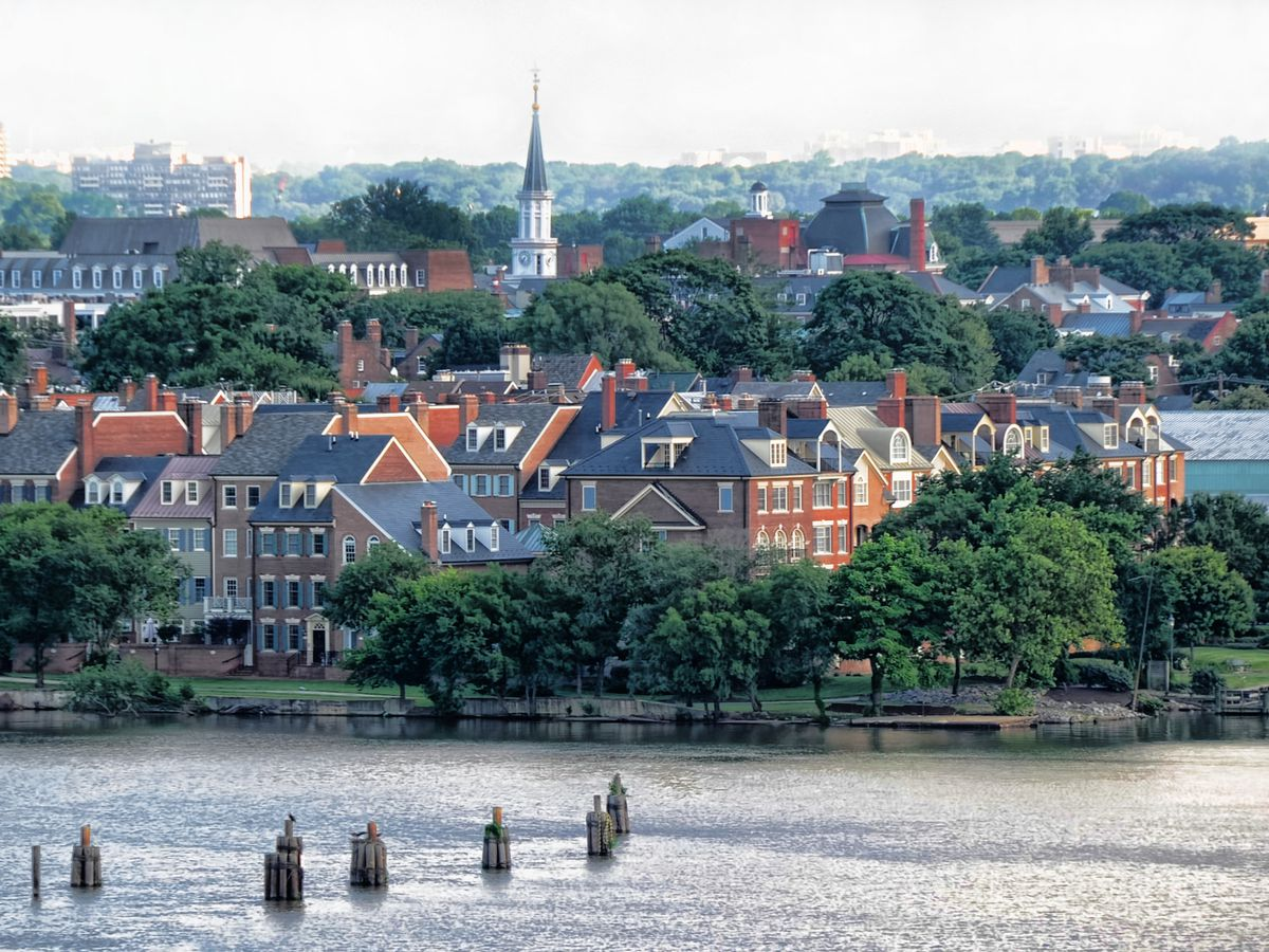 A historic town along a river. It features Colonial homes and a church spire.