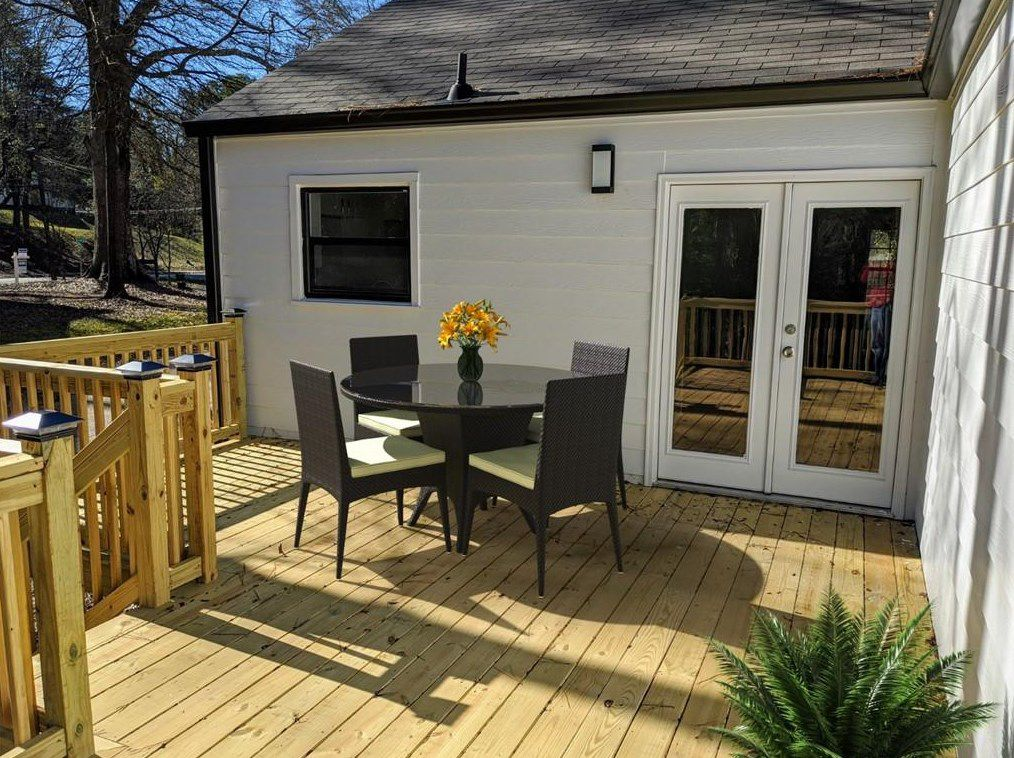 A wooden deck with white walls.