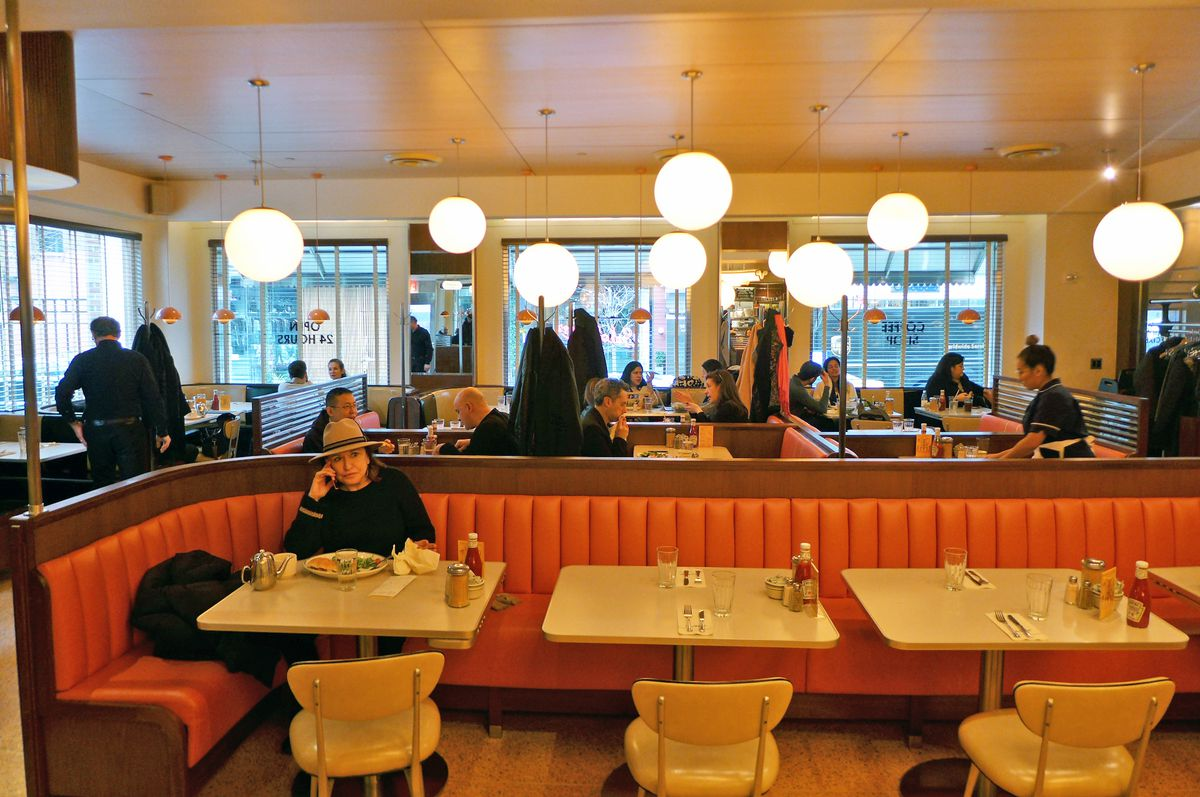 A long banquette with a single lady wearing at hat sitting at it, globe lights overhead.