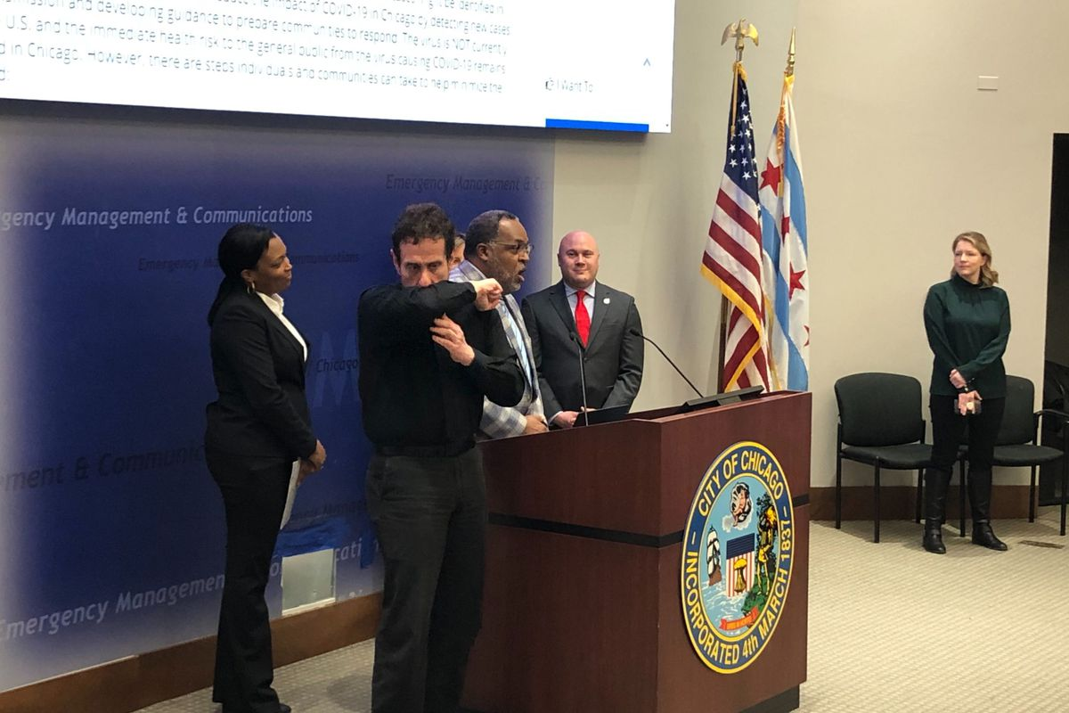 An interpreter demonstrates a proper coughing technique at a Tuesday press conference attended by Chicago schools chief Janice Jackson, left, the district's Chief Health Officer Kenneth Fox, speaking, and Jennifer Layden, far right, deputy commissioner for the city's health department.