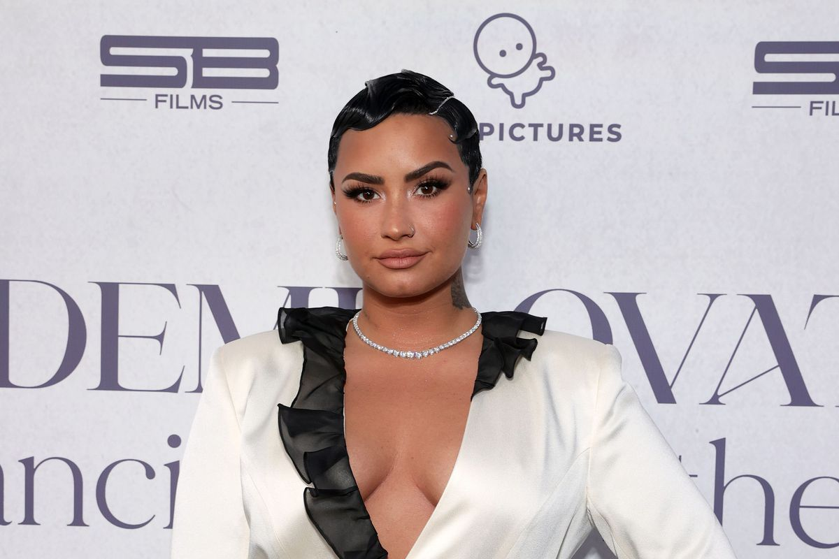 """Demi Lovato stands in front of a step-and-repeat for her docu-series """"Dancing With the Devil,"""" wearing a white blazer with black trim and a pixie cut."""