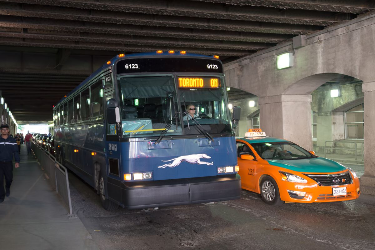 Greyhound bus and Beck taxi under an elevated bridge in...