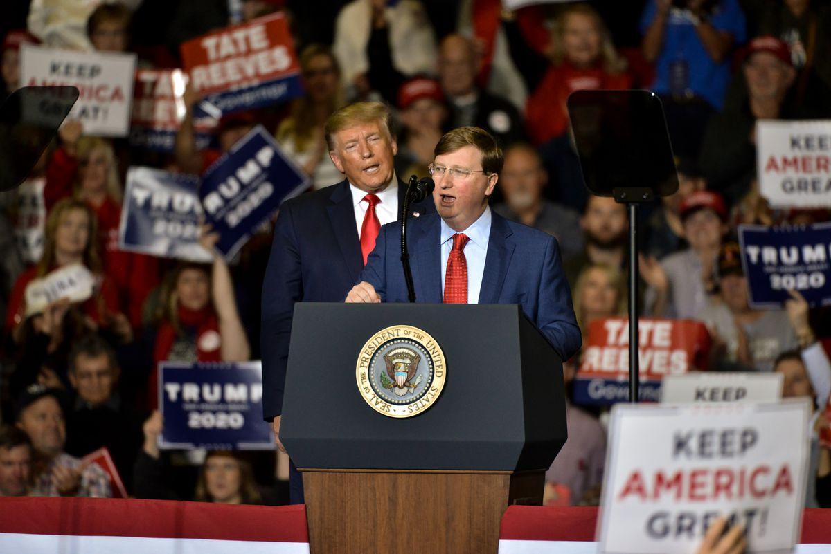 Trump looms behind Reeves as a crowd waving Trump Pence 2020 signs cheers.