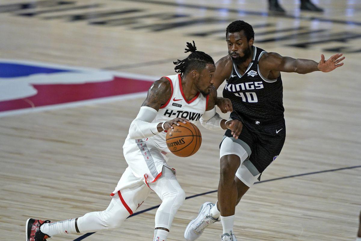 Houston Rockets' Robert Covington (33), left, drives around Sacramento Kings' Harrison Barnes (40) during the first half of an NBA basketball game Sunday, Aug. 9, 2020