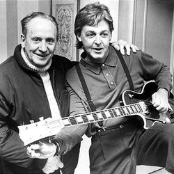 """In this May 3, 1988 file photo, Paul McCartney, right, tries out a custom-made left handed """"Les Paul Lite"""" guitar presented to him by designer, Les Paul, left, in New York."""