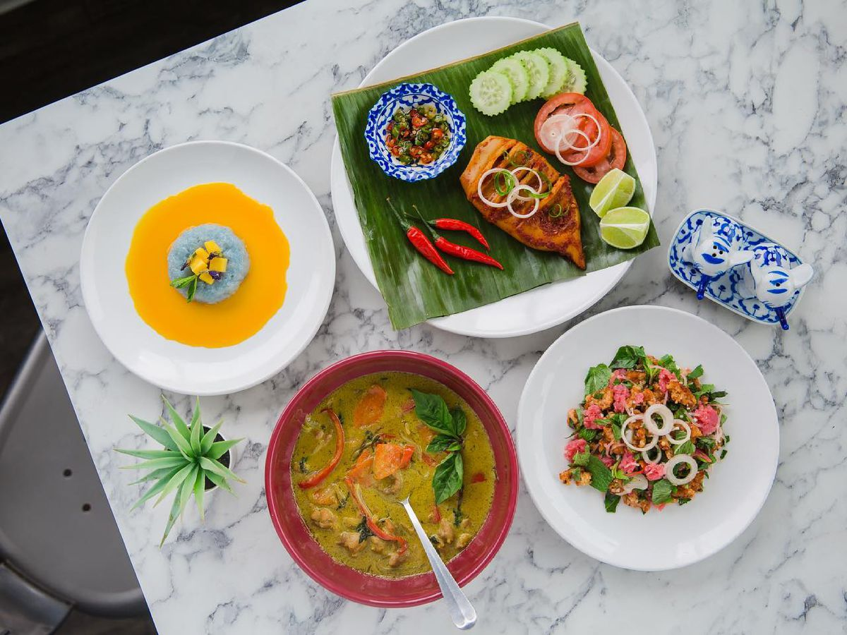 A top-down view of dishes at D'Bali Asian Bistro, including a curry stew at the bottom