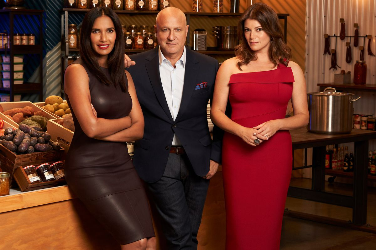 Padma Lakshmi, Tom Colicchio, and Gail Simmons dressed up and leaning against a table overflowing with ingredients.