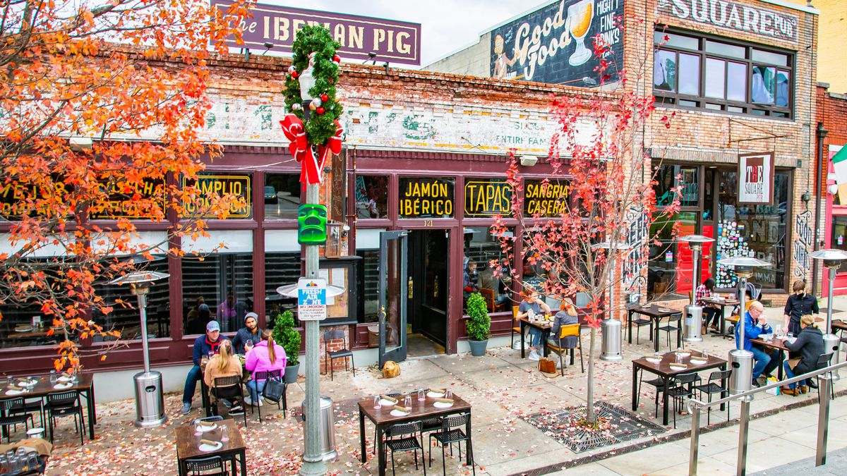 The Iberian Pig, in a low brick building with yellow neon signs; there are people dining at tables along a fall leave-covered sidewalk.