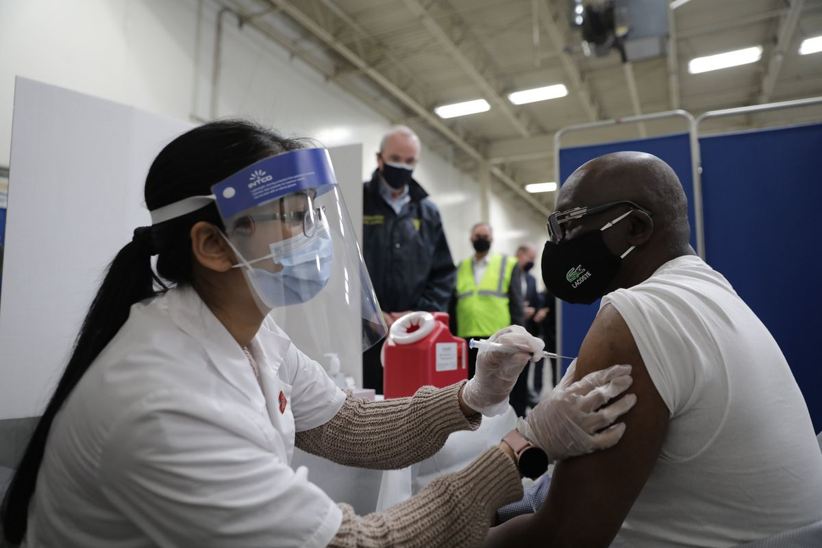 A healthcare worker wearing a face shield and mask gives a shot of a COVID vaccine to a man wearing a black mask and glasses.