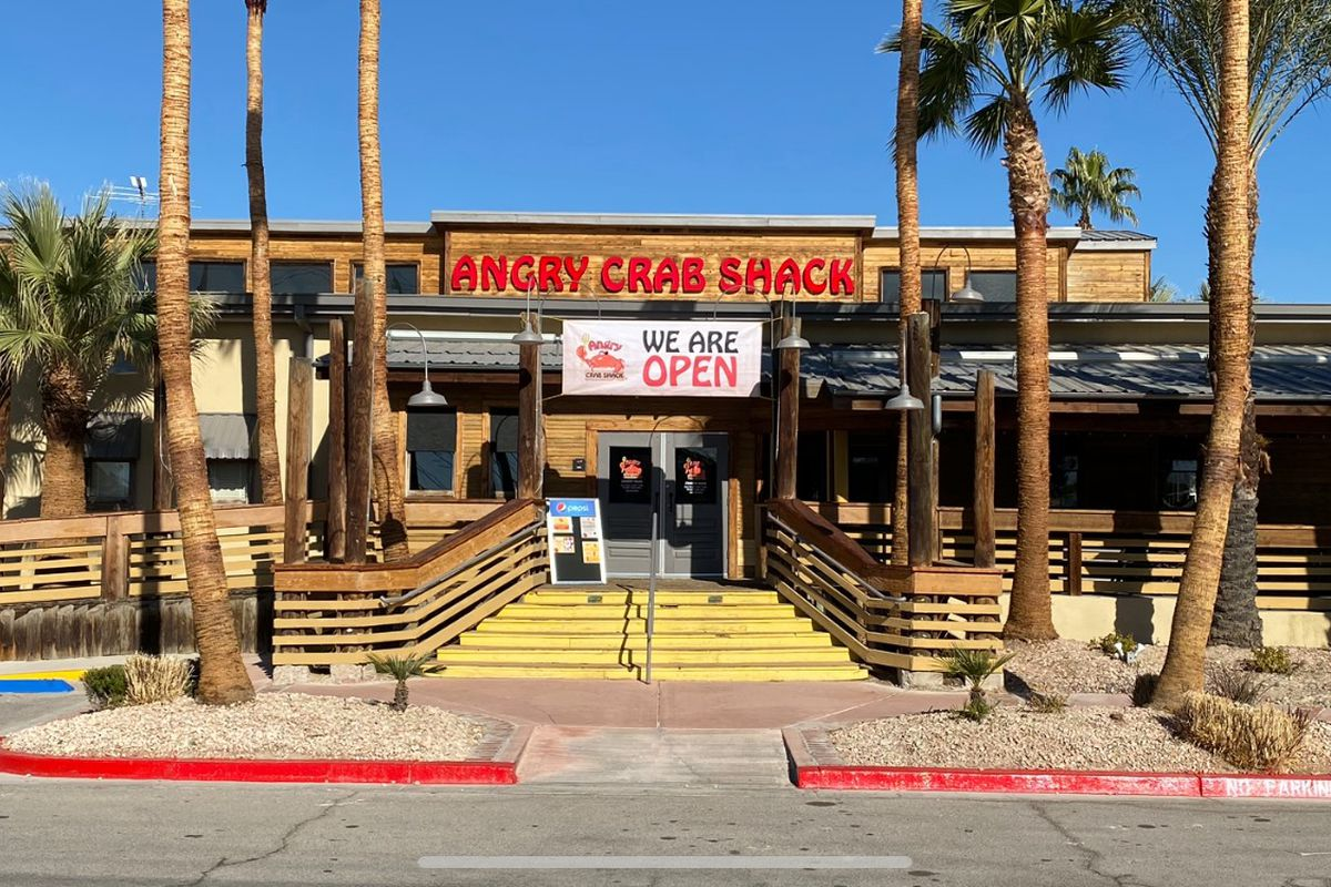 The exterior of a restaurant with yellow steps in front and palm trees on either side