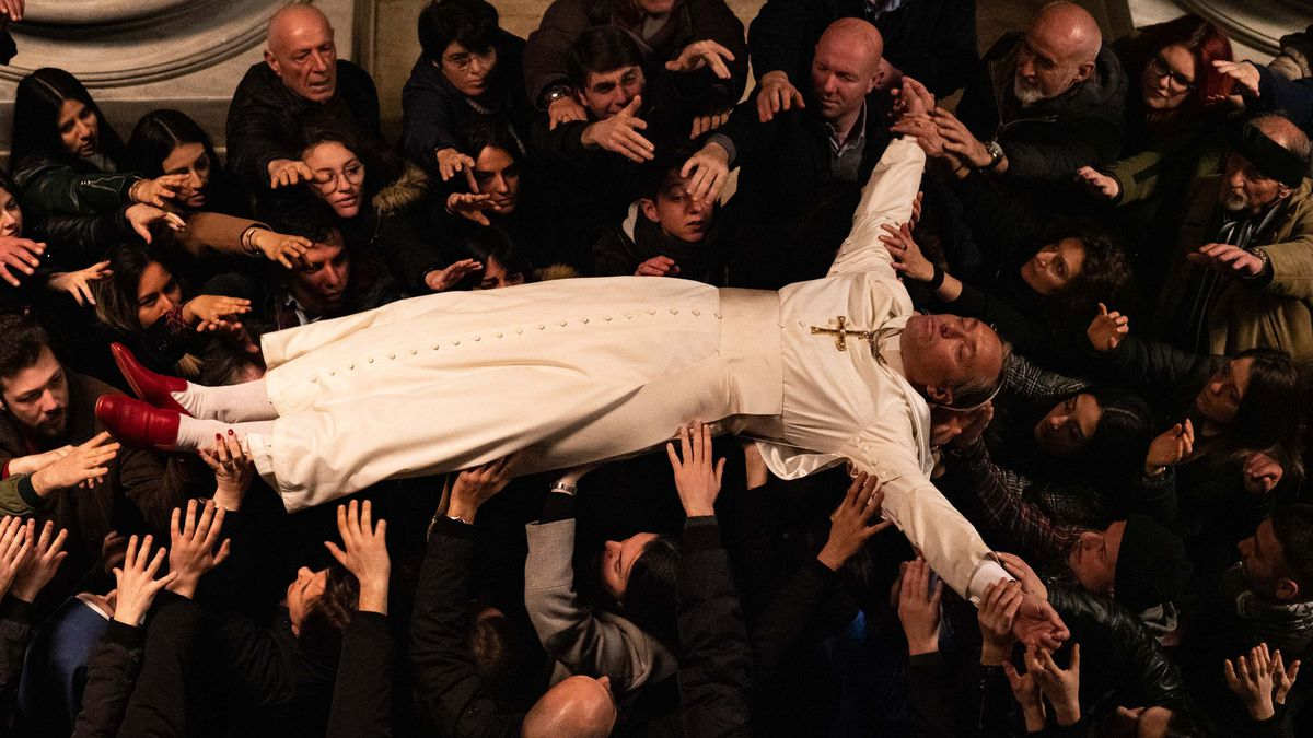 Jude Law as the Pope in The New Pope stretches out on his back, dressed in white robes and vivid red loafers, and is borne aloft in a crucifixion position by dozens of followers dressed in all black.