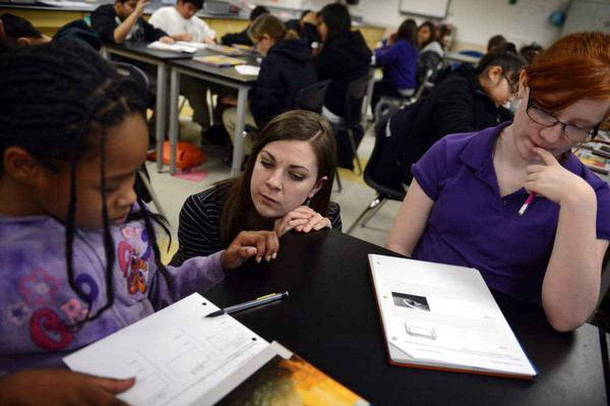 Sixth-grade science teacher Monica Wisniewski works with Pija Williams Terralee, left, and Myth Cubbison at Kearney Middle School in Commerce City. Kearney is in Adams County School District 14.