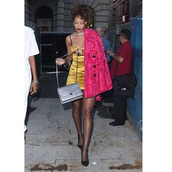 And on the last day of NYFW, <strong>Rihanna</strong> went bright in a yellow satin dress, with a pink fuzzy coat hanging off her shoulder and stockings.