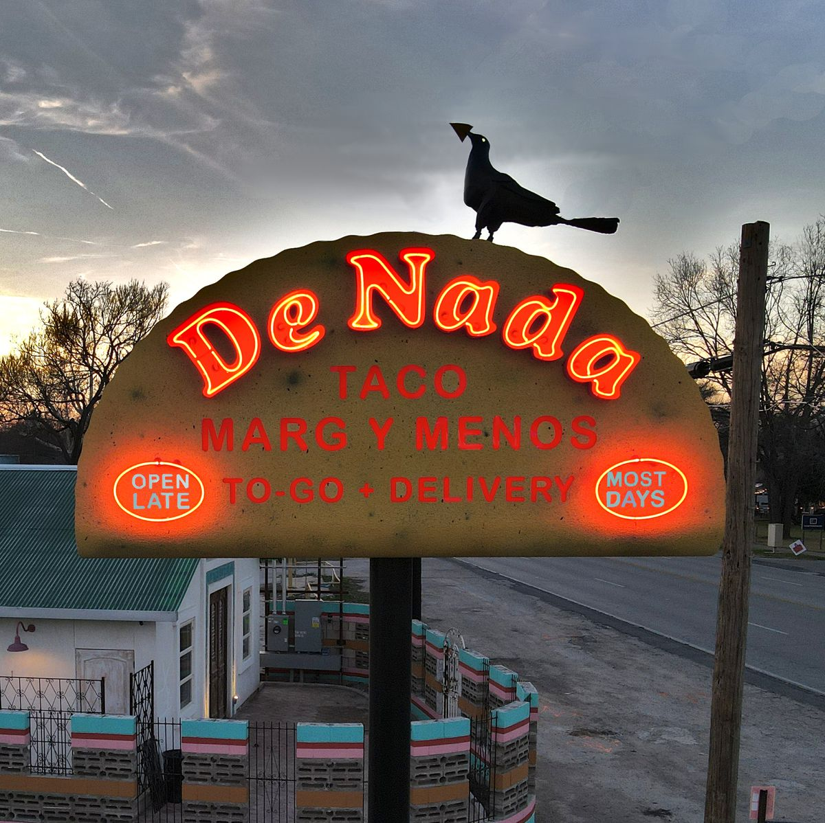 A lit sign that says De Nada Tacos Margs Y Menos Takeout and Delivery. There's a grackle on top.