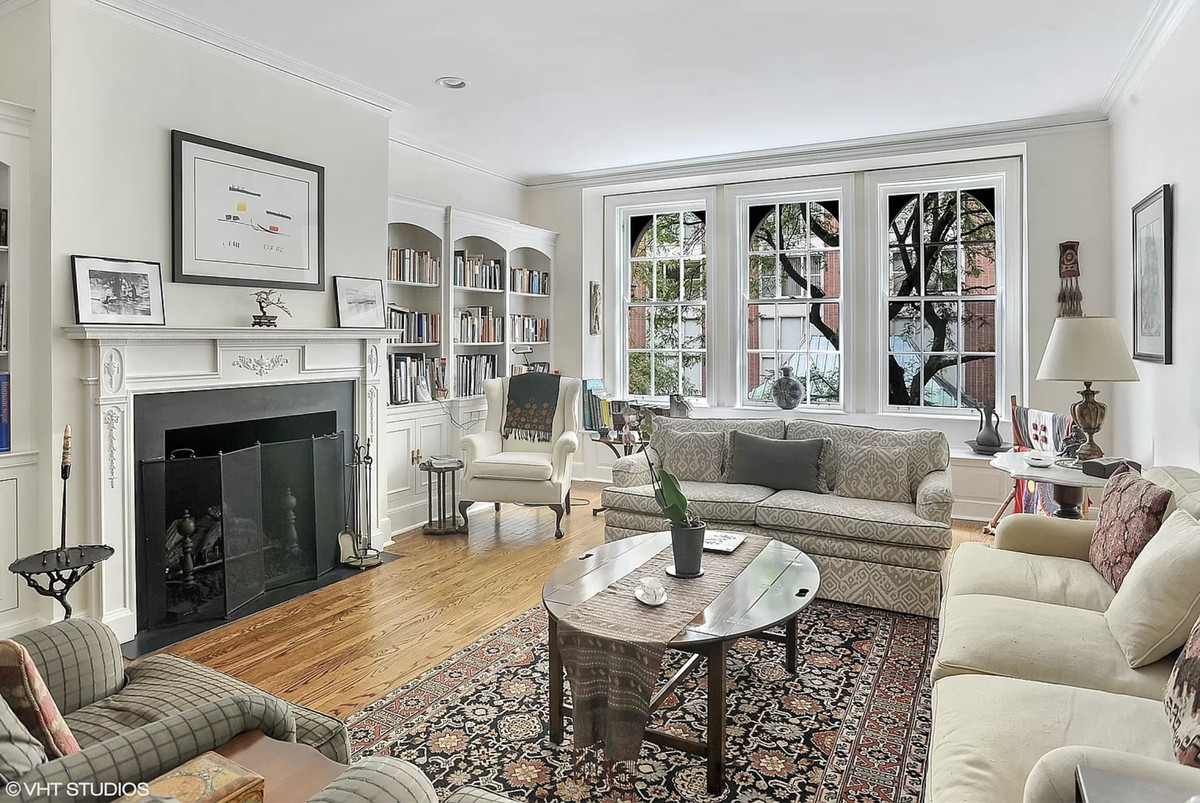 A living room with black and white fireplace, couches around a coffee table, built-in bookcases, and a large window.