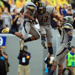 West Virginia players, from left, Tavon Austin, Andrew Buie and Stedman Bailey celebrate Austin's touchdown during an NCAA college football game against the University of Maryland in Morgantown, W.Va., Saturday, Sept. 22, 2012.