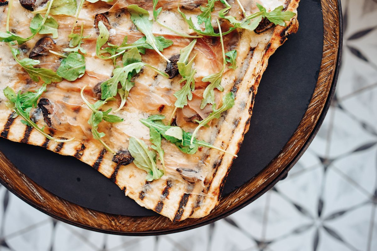 Overhead shot of a very thin grilled pizza — with distinct grill lines throughout —topped with arugula, dots of fig jam, and thinly sliced prosciutto. It sits on a black table with a wooden perimeter over a tiled floor.
