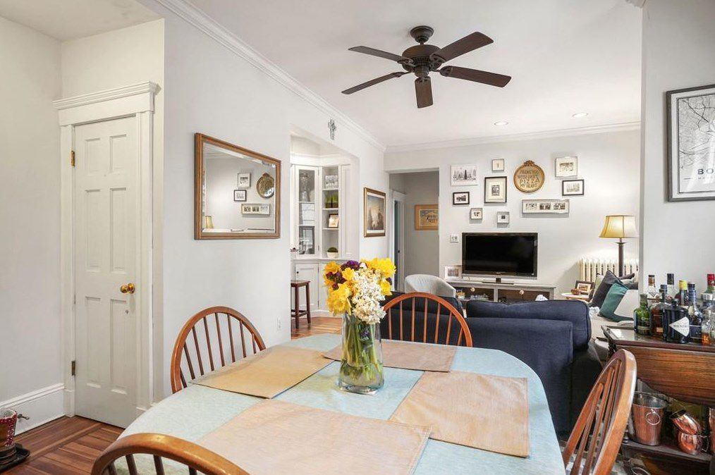 An open dining room with a table and chairs and a ceiling fan above the able.