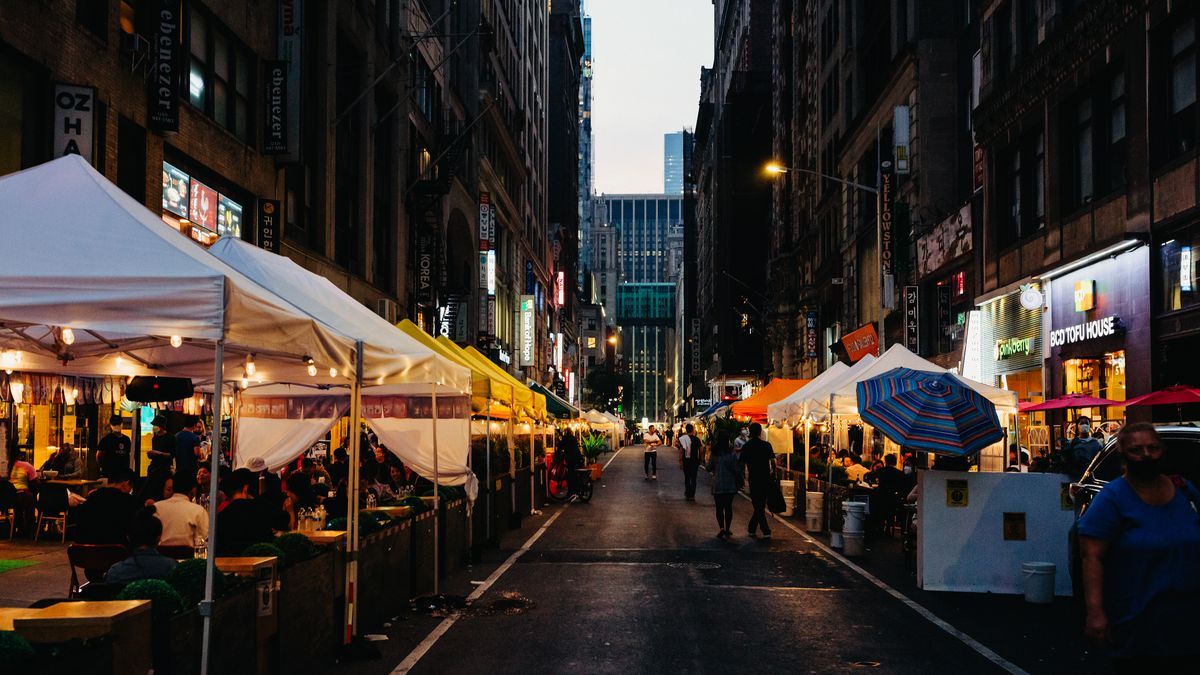 A closed-off street in New York City with pedestrians walking and a row of white tents for outdoor dining
