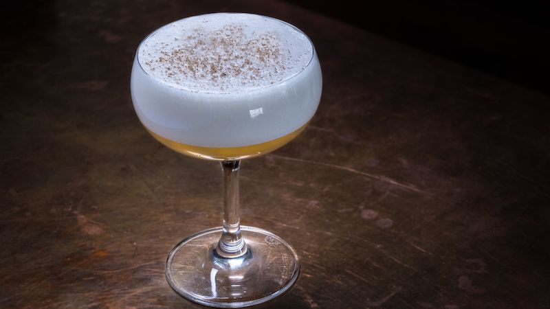 A stemmed cocktail glass with a yellow cocktail topped with white foam.