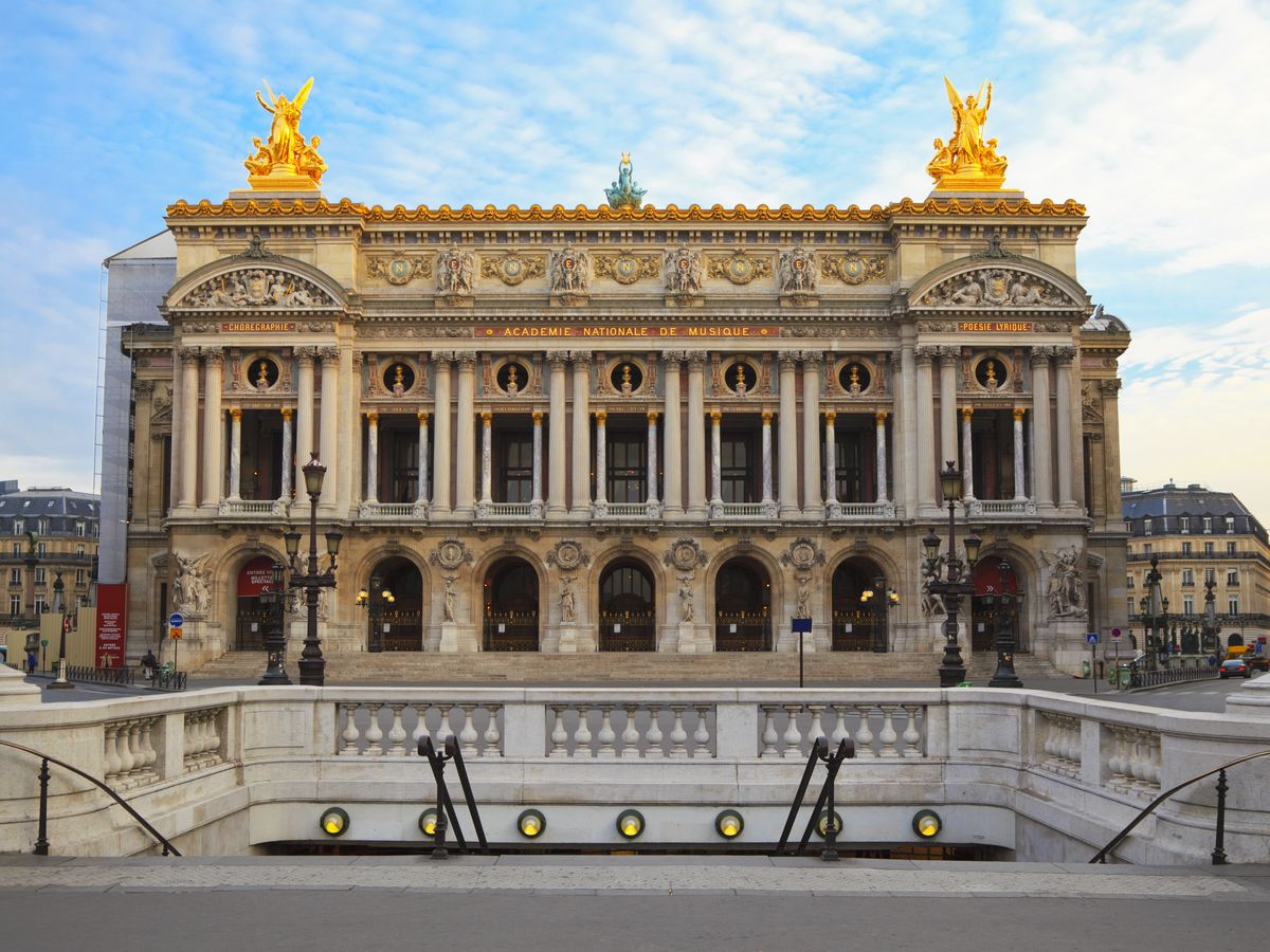 The exterior of Palais Garnier in Paris. The facade is tan with many columns and a gold roof with golden statues arranged at each roof corner.