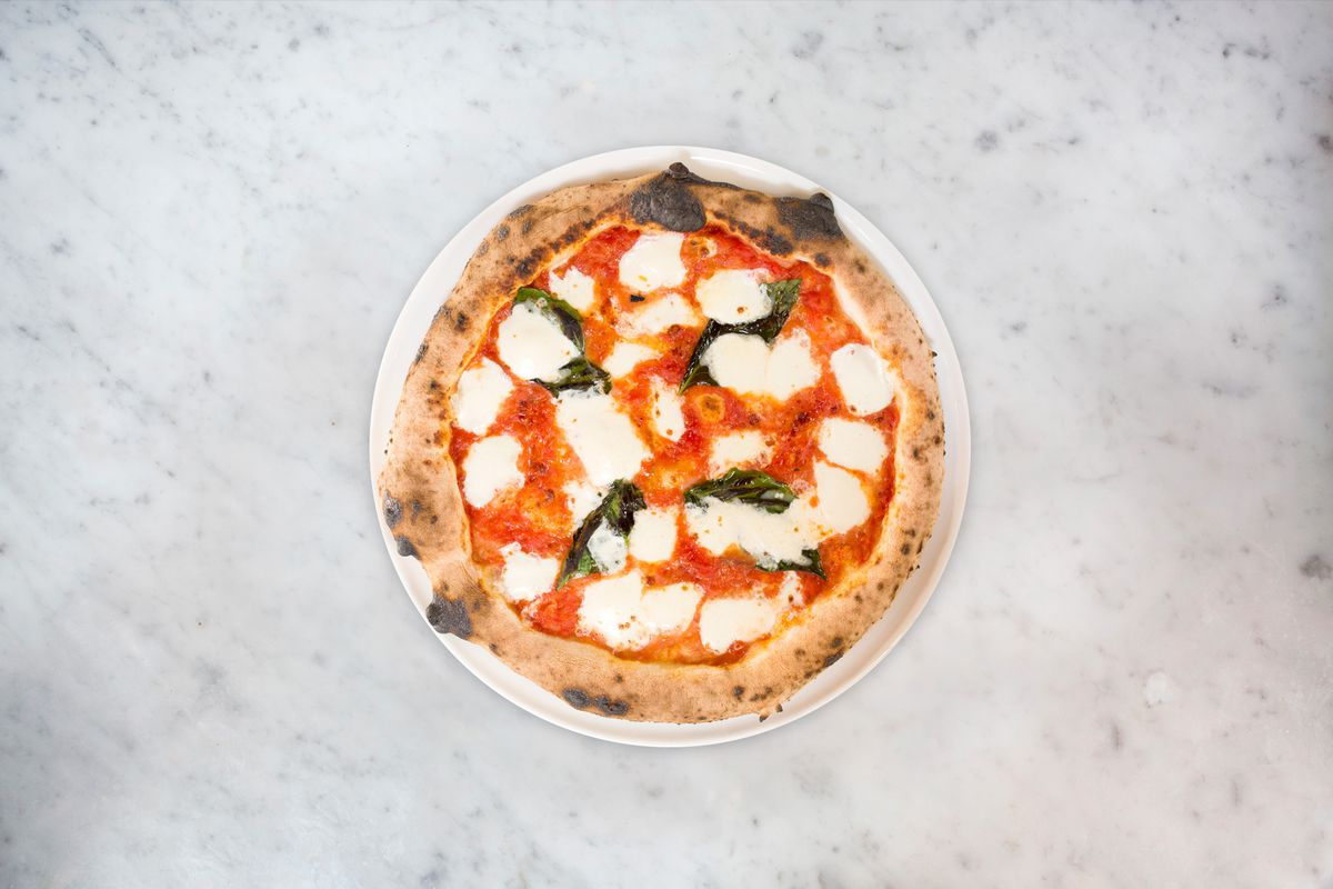 overhead shot of a margherita pizza on a marble counter