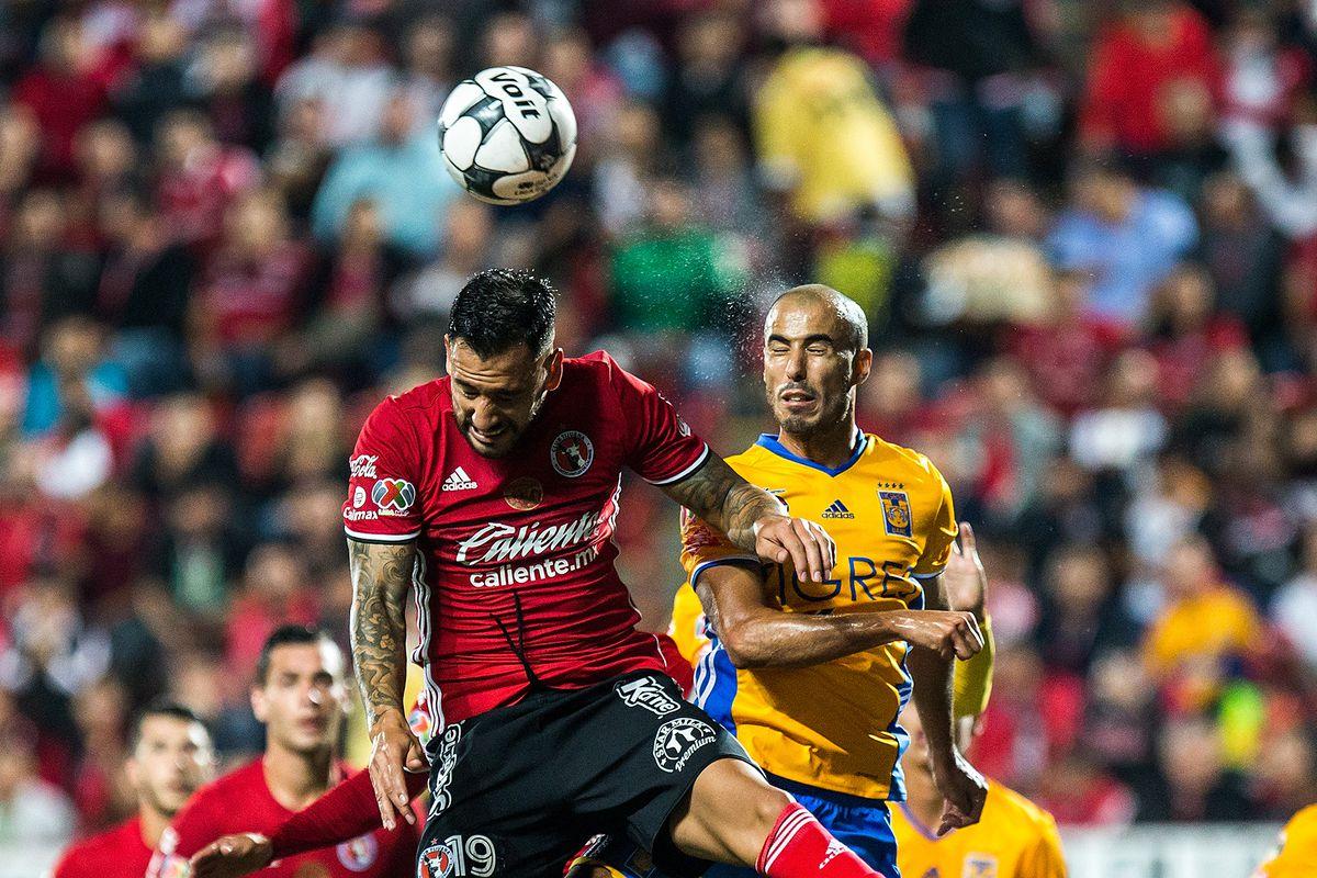 Tijuana's Milton Caraglio goes up for a header against Tigres UANL.