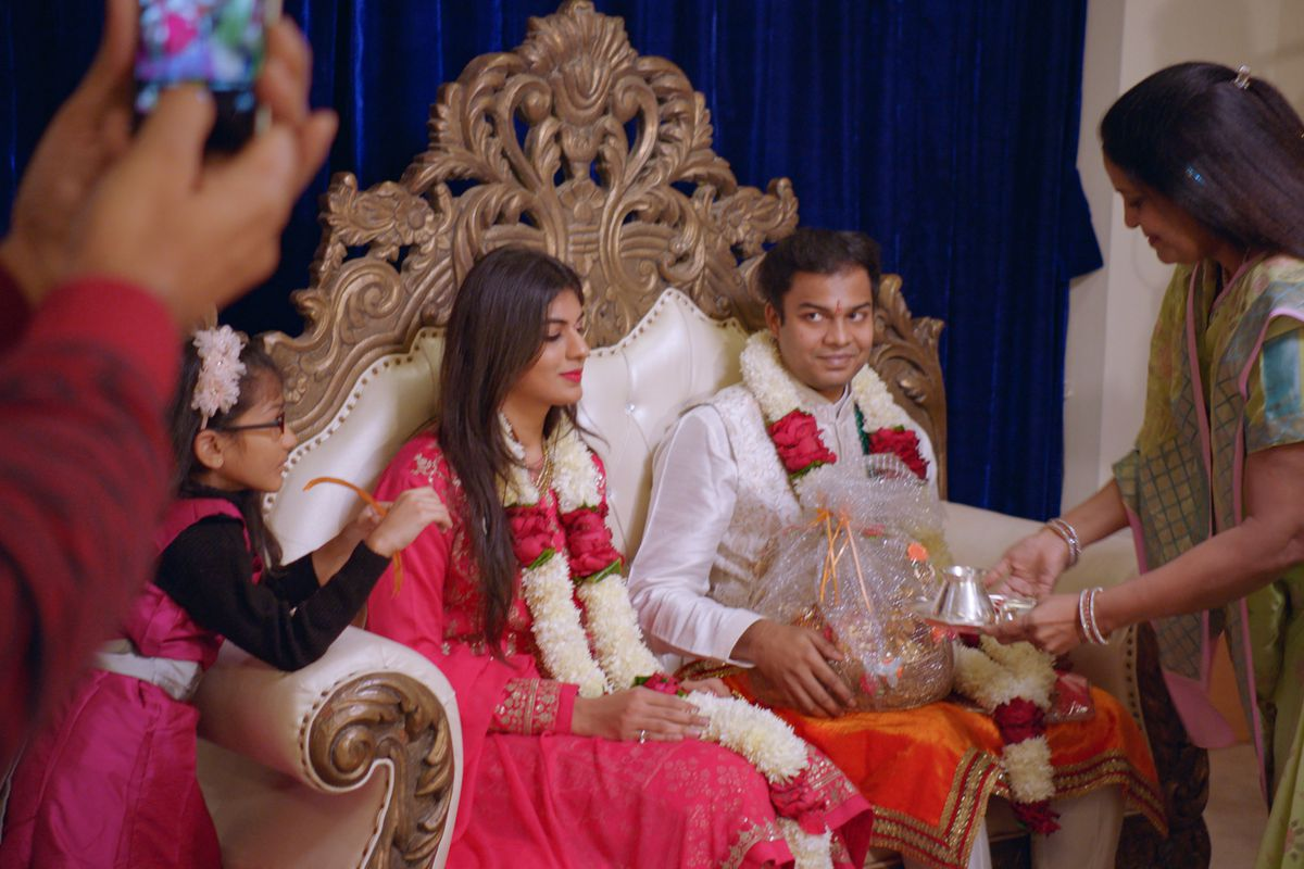 A couple sits together on an elaborate gold throne-style loveseat in Netflix's Indian Matchmaking.