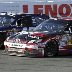 Denny Hamlin (11) competes against Jimmie Johnson during the final restart in the NASCAR Sprint Cup Series auto race at New Hampshire Motor Speedway, Sunday, Sept. 23, 2012, in Loudon, N.H. Hamlin won the race, and Johnson finished second.