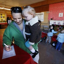 Danielle Andrus holds her daughter Naomi as she writes a thank you note during 2014 Operation Chimney Drop at Head Start in Salt Lake City, Monday, Dec. 15, 2014.