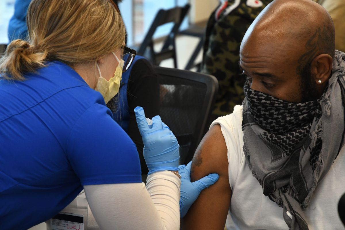 A woman wearing gloves and a mask gives a vaccine to a man wearing a mask.
