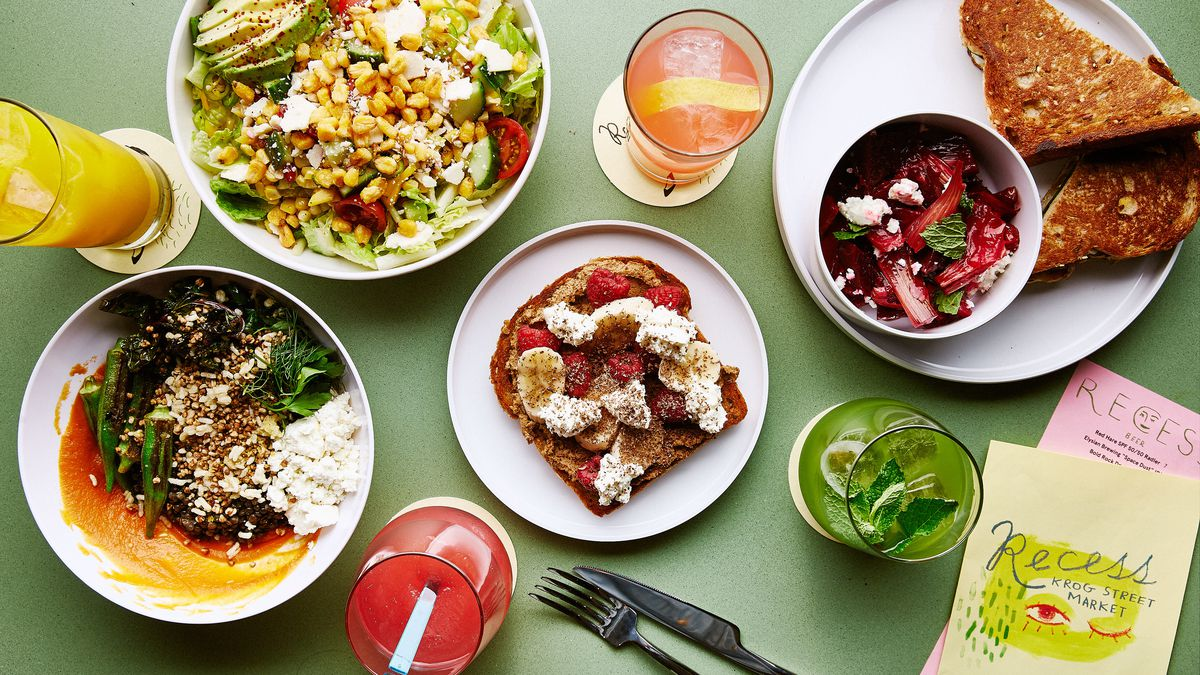 Several grain bowls, strawberry and cheese toast, and fresh-pressed juices on a light green table