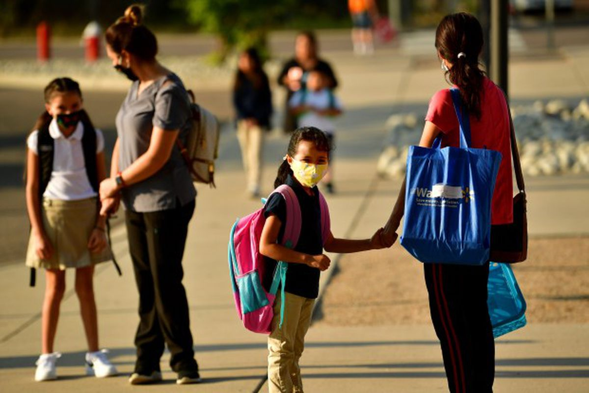 Fernanda Dominguez, 6, center, holds the hand of her mother Guadalupe Chavez, right, as Fernanda waits to be escorted to her classroom by faculty members on first day of school at Hodgkins Leadership Academy in Westminster on Thursday. Aug. 20, 2020.