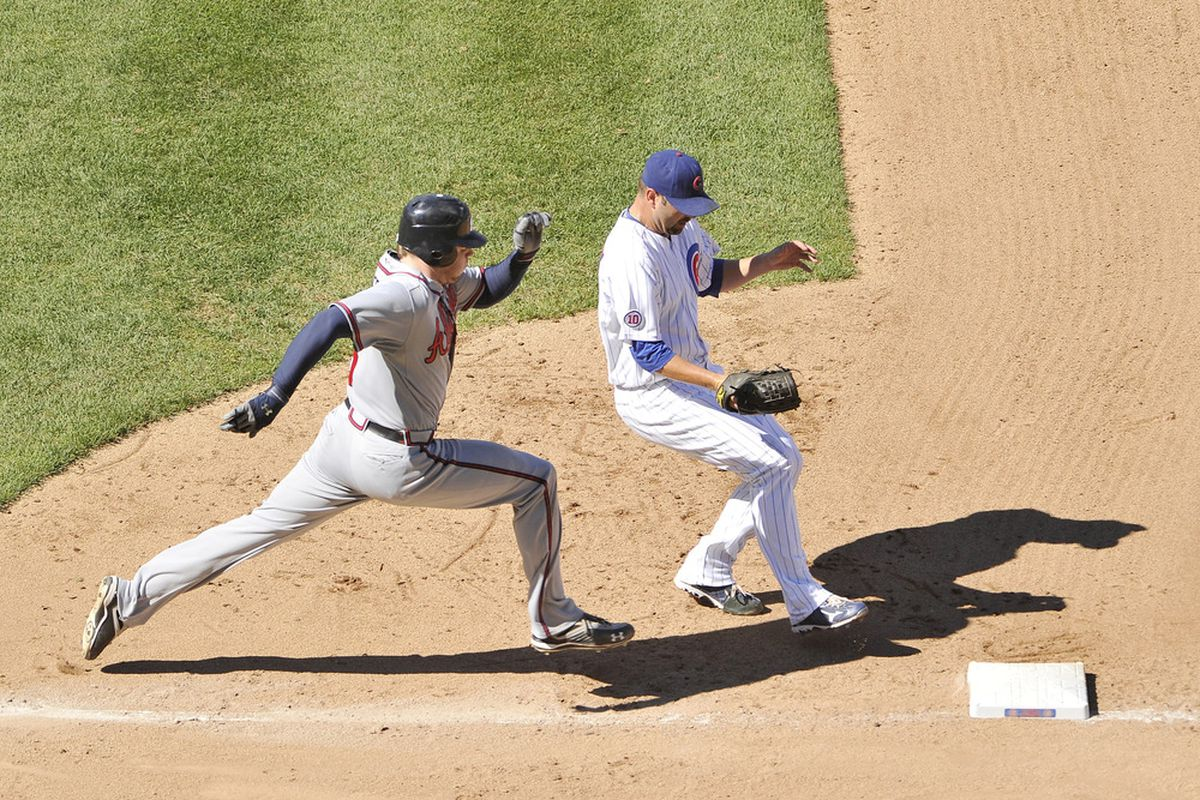 Pitcher John Grabow of the Chicago Cubs beats Freddie Freeman of the Atlanta Braves to the bag after Freeman hit a ground ball to first base during the seventh inning at Wrigley Field in Chicago, Illinois.  (Photo by Brian Kersey/Getty Images)
