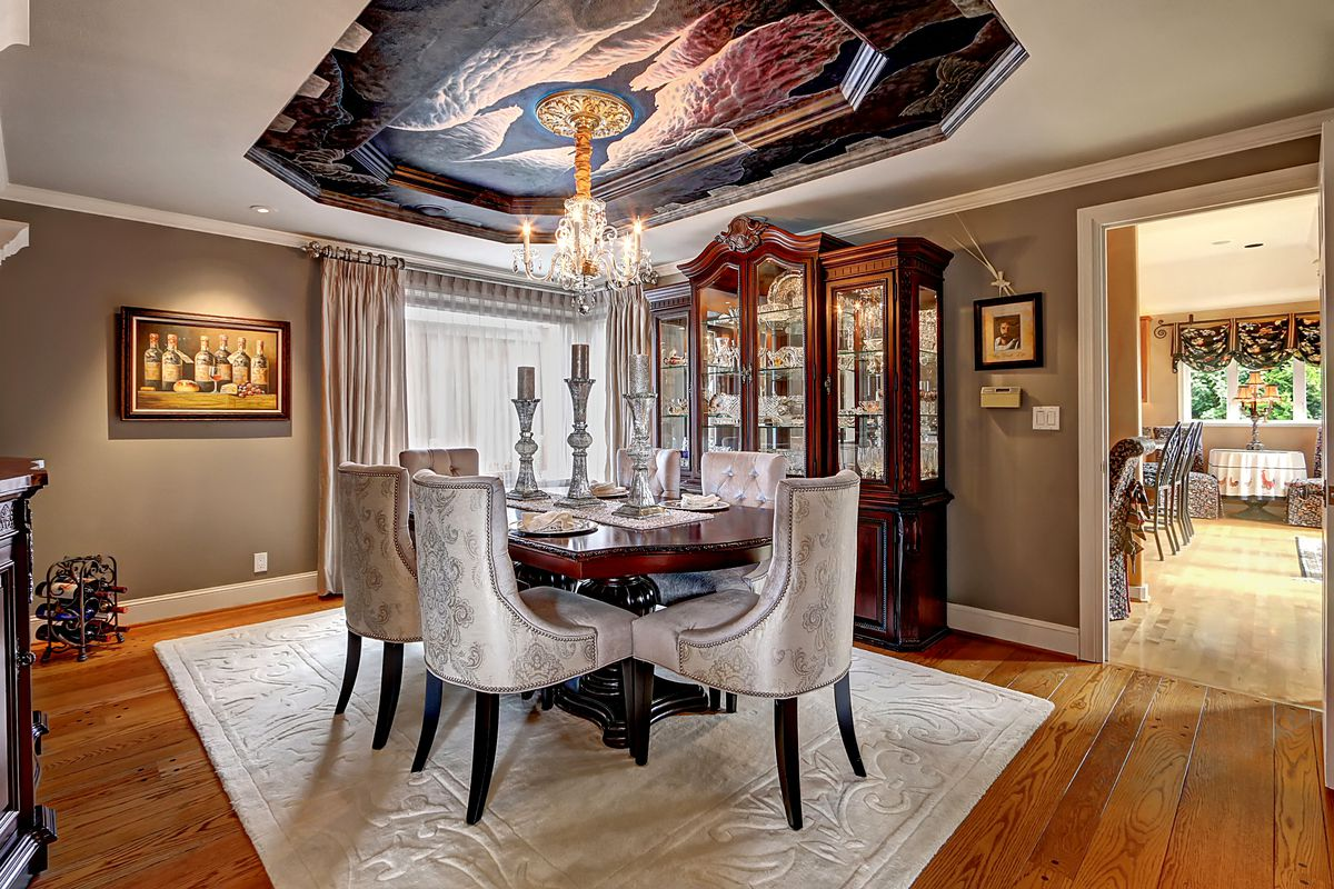 A dining room with a recessed ceiling alcove with a winged mural and a chandelier in the middle.
