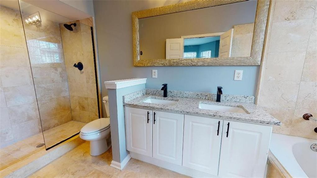 Bathroom with double vanity, toilet, glass shower and separate soaking tub.