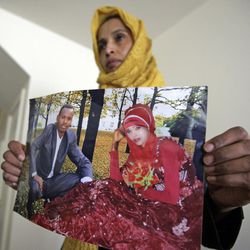 Somali refugee Nimo Hashi holds a photo of her husband Tuesday, Jan. 31, 2017,  in Salt Lake City. Hashi bought a new kitchen table and couches for her Salt Lake City apartment in joyful anticipation of reuniting Friday with her husband for the first time in nearly three years. But he won't be arriving as planned to see her and the 2-year-old daughter he's never met. He is among hundreds of people stuck in limbo after President Donald Trump's executive order temporarily banned refugees and nearly all travelers from seven Muslim-majority countries, including Somalia. (AP Photo/Rick Bowmer)