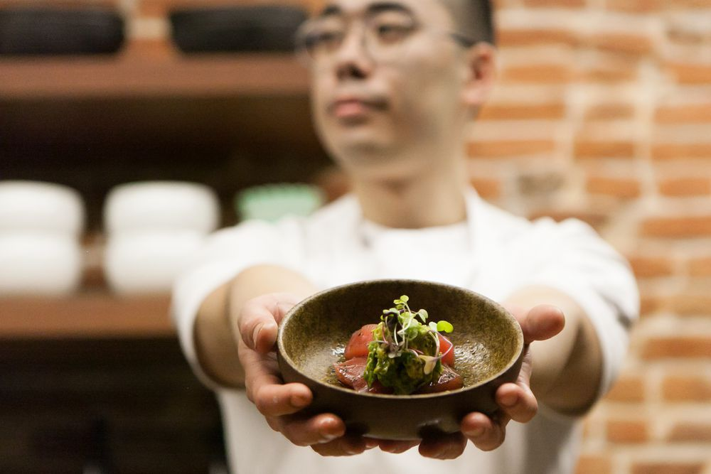 man holding a bowl with sushi fish inside