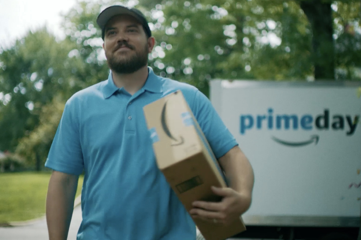 A smiling man delivers an Amazon Prime package.