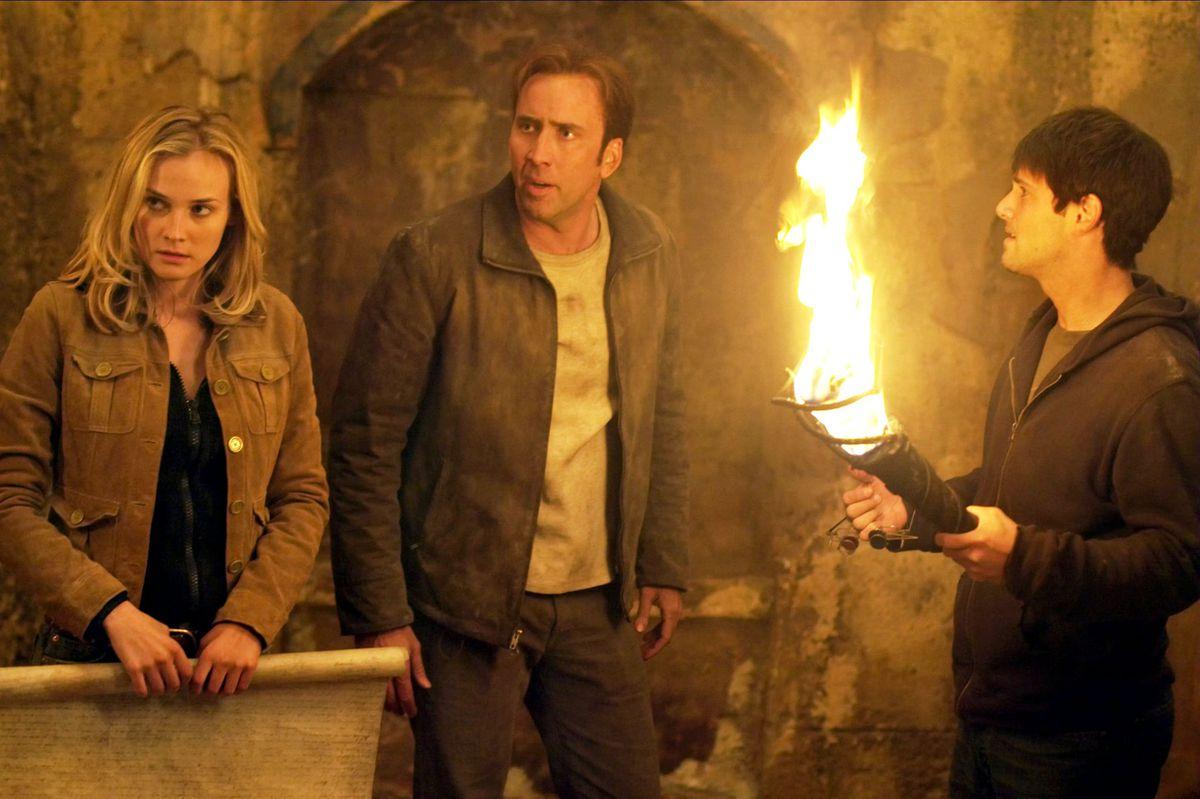 Abigail Chase (Diane Kruger), Benjamin Franklin Gates (Nicolas Cage) y Riley Poole (Justin Bartha) en una tumba subterránea en National Treasure.