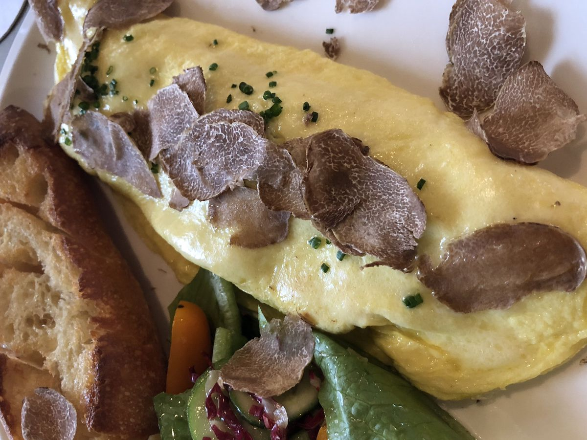 A rolled omelette with some greens, toast, and white truffles shaved atop.